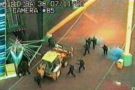Armed police surround the digger used by the raiders in 2000