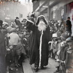 Father Christmas is surrounded by excited schoolchildren as he arrives at the Arding and Hobbs department store on November 2, 1926, in Clapham Junction, London