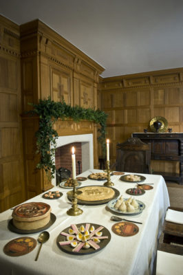 A view of the 1630 period room at Christmas Past. The photograph sows the table laid for a feast of sweetmeats and the mantel above the fireplace decorated with evergreens.