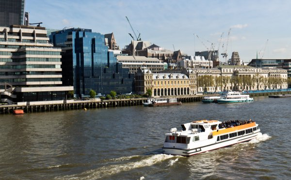 A water taxi transports people along the River Thames in London, England