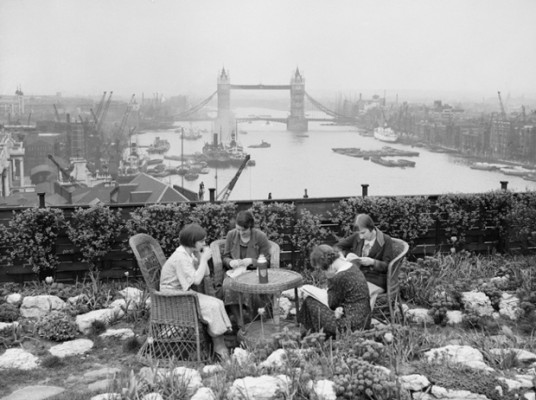 Four women have lunch in the roof garden on Adelaide House, overlooking the River Thames and Tower Bridge, c. 1934.