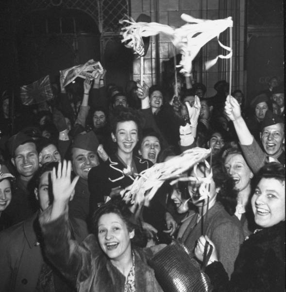 Civilians and soldiers celebrating in London.