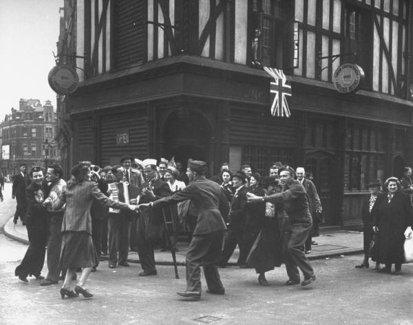 Injured musicians play while civilians and soldiers do an impromptu dance in the streets on VE Day to celebrate the end of WWII in Europe